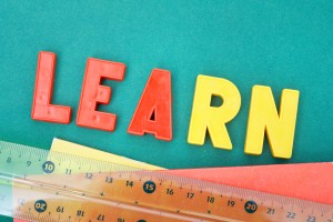 Image of word 'learn' with copybooks and ruler below